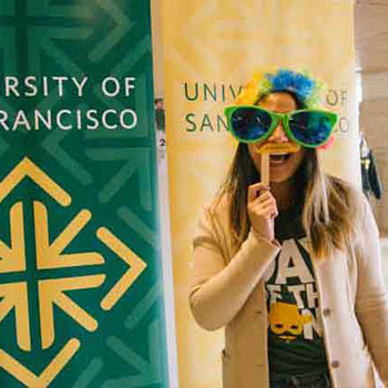 Student in front of a sign reading University of San Francisco wears a set of oversize glasses as a mask.
