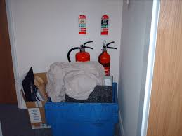 Example of fire extinguishers that are blocked by a recycling bin.