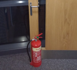 Example of a fire door being propped open by a fire extinguisher.