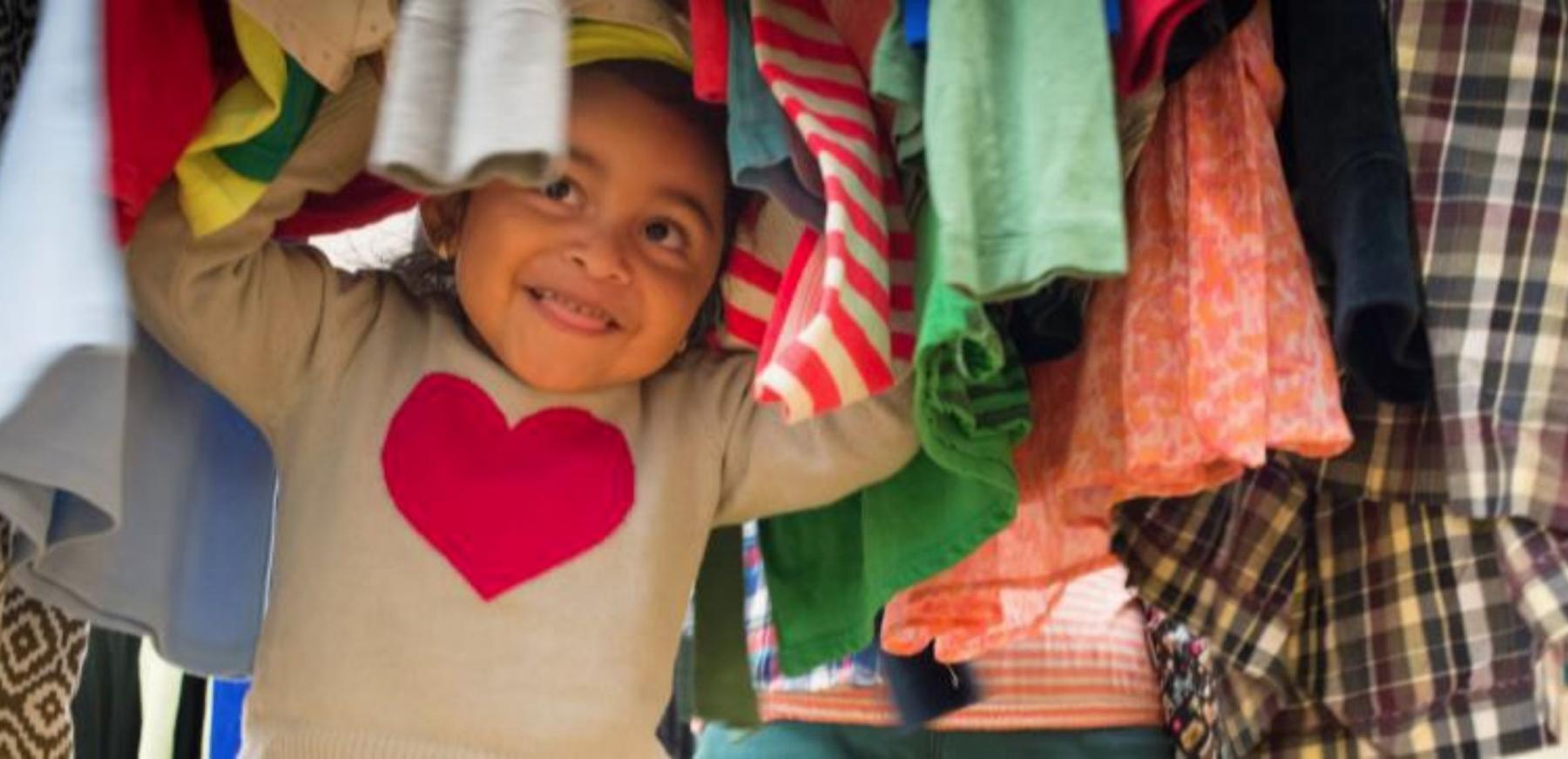 Smiling child underneath a rack of donated clothes.