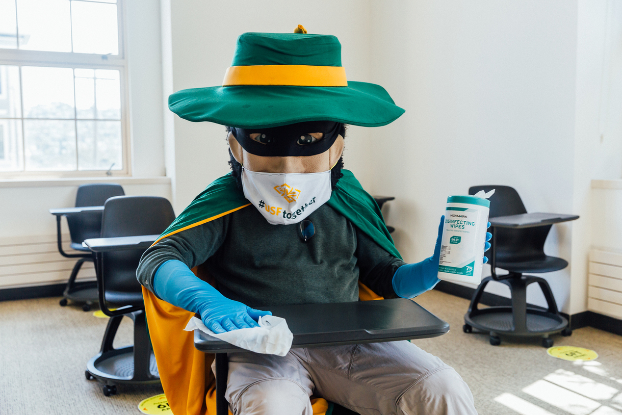 USF Mascot sitting at a desk wearing a mask and using Disinfecting Wipes to sanitize the table