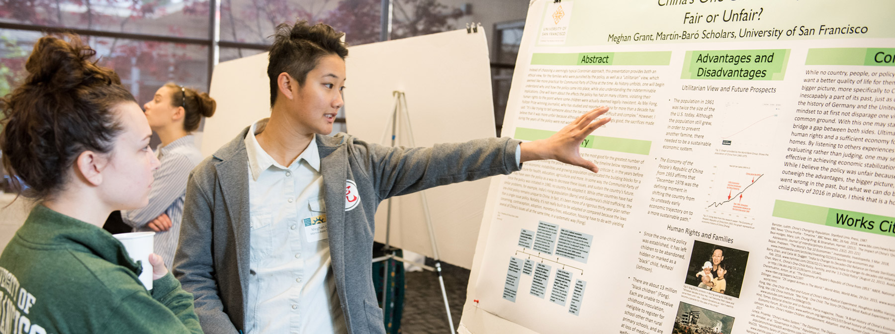 Student explaining research presentation to CARD attendee