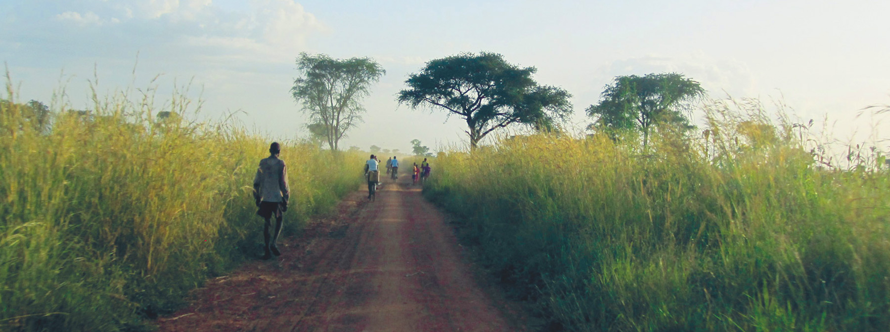 African villagers walking on a dirt road surrounded by tall green grass