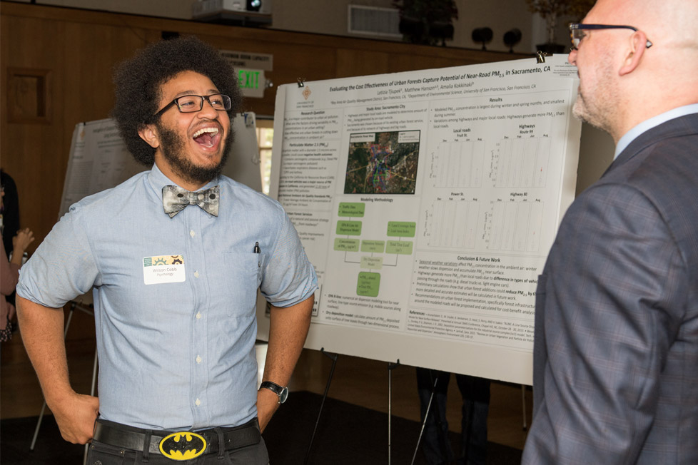 Student presents his research to an attendee