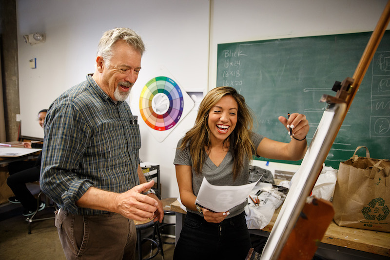 Photograph of an art student and instructor pointing excitedly at an easel with artwork