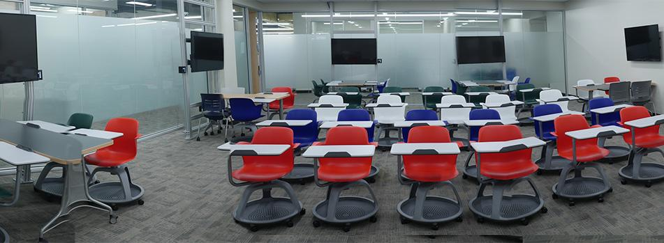 Gleeson 213 active learning classroom with colored rolling chairs and multiple screens