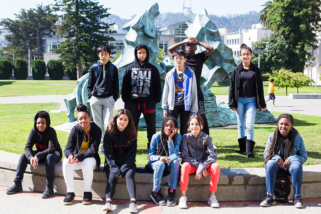students in front of statue in library