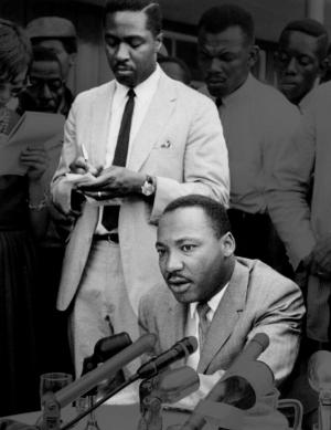 Black and white photo of Martin Luther King Jr sitting and speaking with Dr. Clarence B. Jones standing behind him.