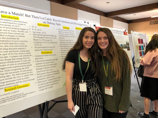 Two student researchers pose with their poster project.