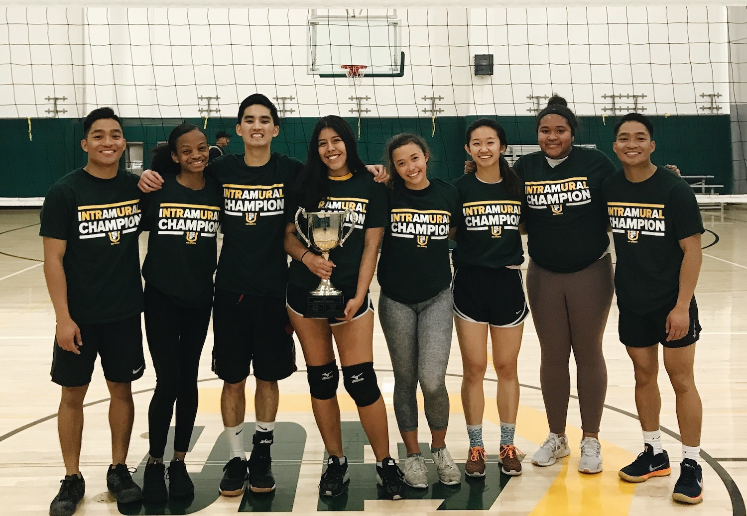Fall 2019 Volleyball Champion Block Party Standing Together with Trophy