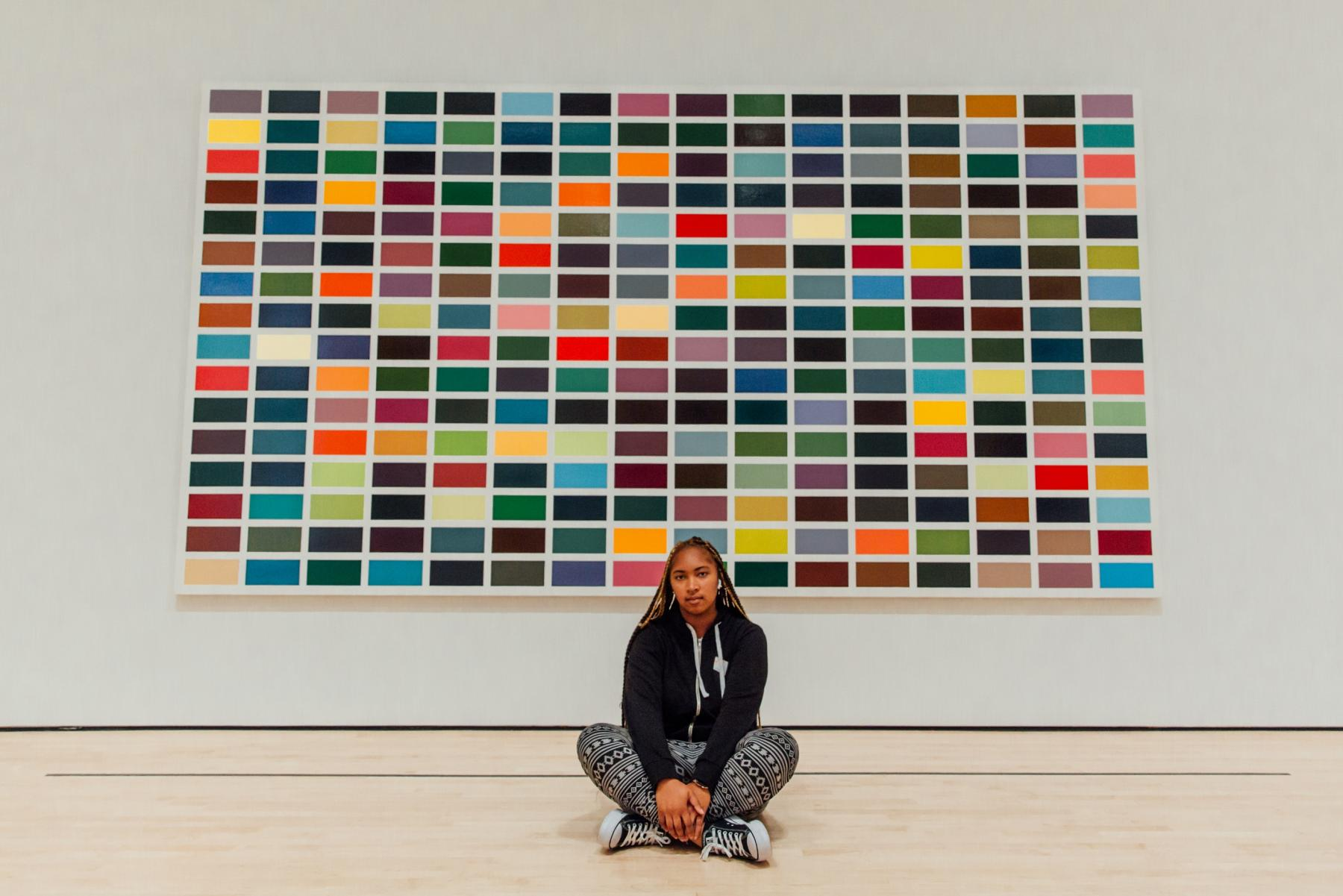 Student sits in front of painting at SF MoMA