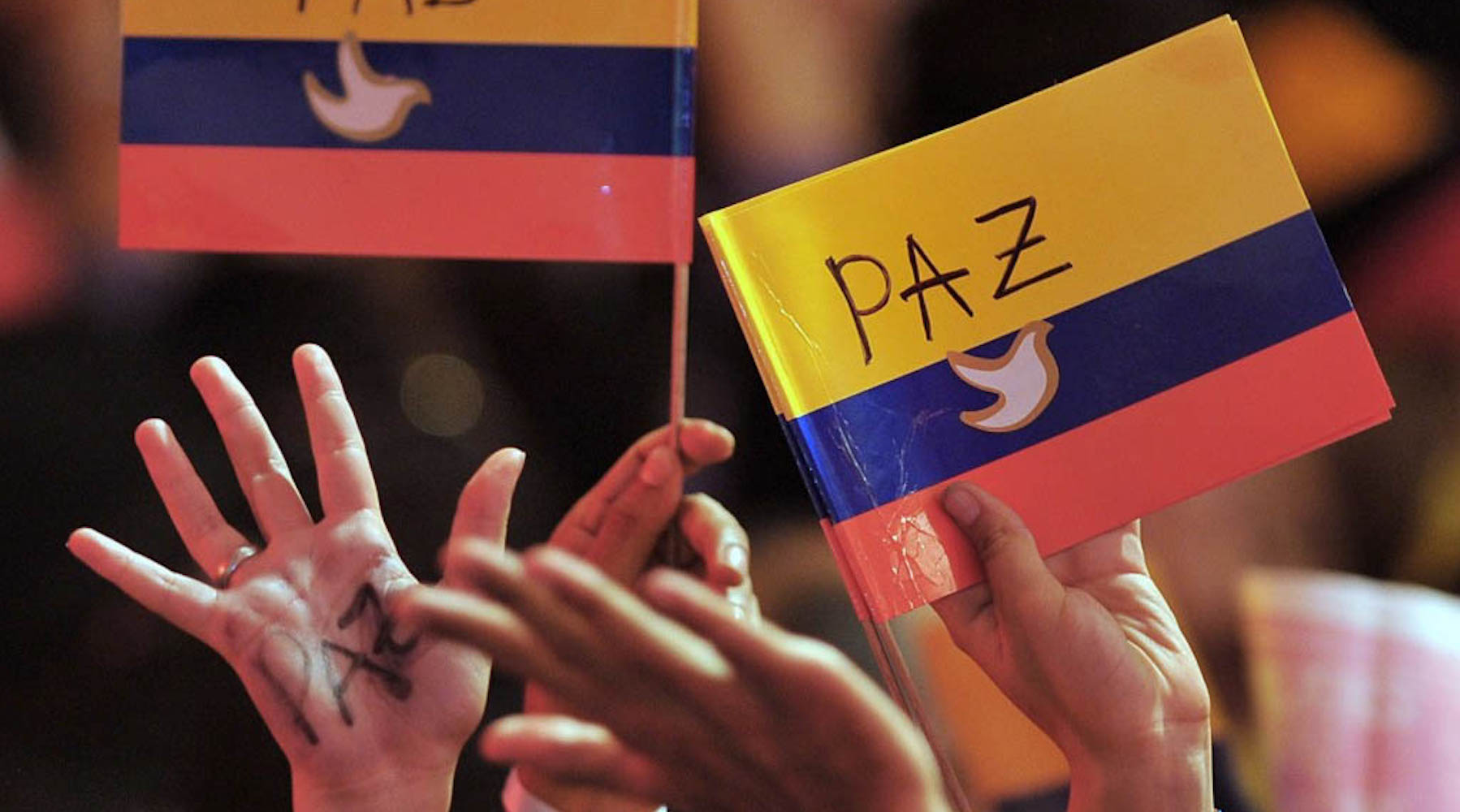 "colombia flags ang raised hands with the word ""pax"" (peace)"
